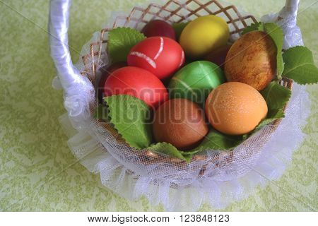 Easter colored eggs in a basket lined with tulle with green mint
