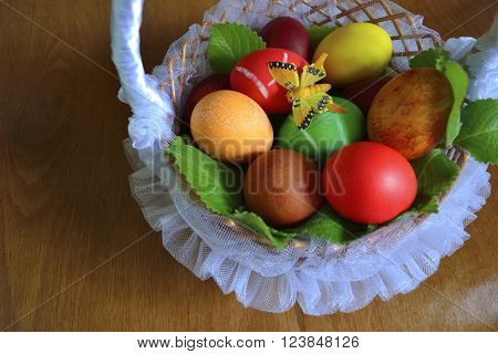 painted eggs for Easter in tulle lined wicker basket with a butterfly