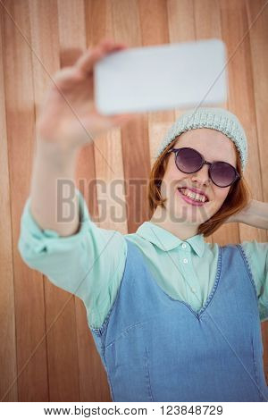 Red haired hipster taking selfie on wooden backgroung