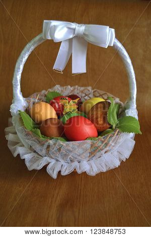 colored eggs for Easter in a wicker basket in tulle with branches mint