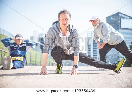 Three senior men doing sport outdoors - Sportive mature people stretching before starting to run outdoors