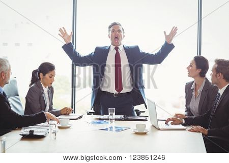 Businessman shouting at his colleagues in conference room during meeting