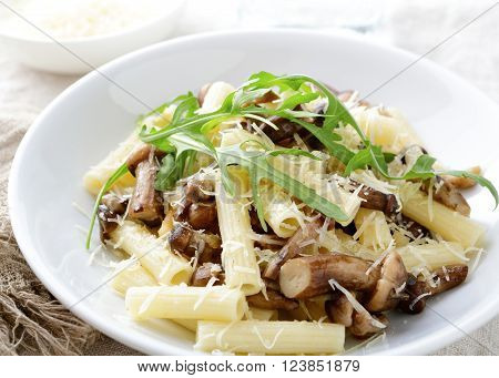 Pasta with mushrooms, arugula and parmesan in white bowl. Traditional italian food