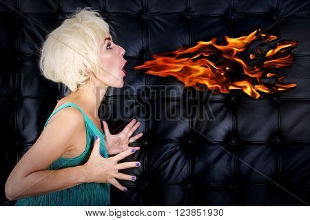 blond woman in green dress spitting fire out of her mouth in front of black leather background