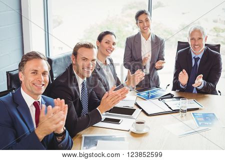 Portrait of businesspeople applauding in conference room during meeting