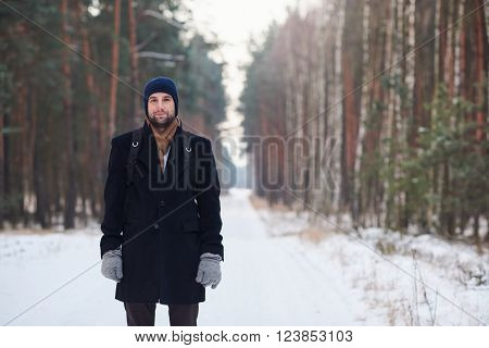 Handsome man wearing beanie, gloves, scarf and a fashionable coat, standing on a road in a forest, with the road covered in snow and large trees on either side