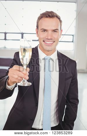 Portrait of young businessman holding champagne flute in the office