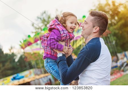 Father holding daughter in his arms having fun at the fun fair, amusement park
