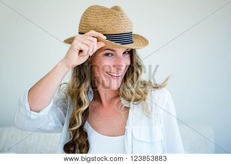 woman wearing a straw fedora, holding the rim of her hat and staring into the distance while smiling
