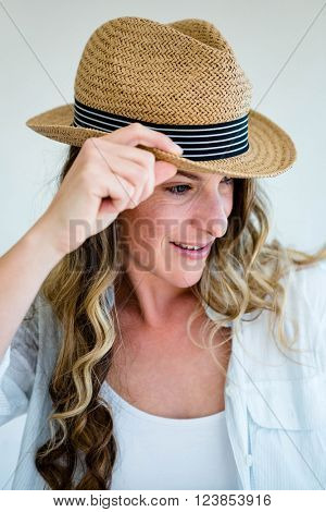 woman wearing a straw fedora, holding the rim of her hat and staring into the distance