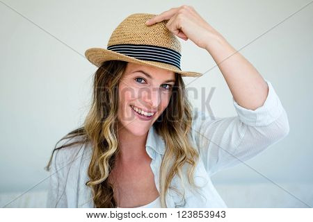 woman wearing a straw fedora, holding the rim of her hat and staring into the camera while smiling