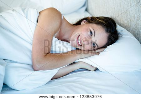 smiling woman lying in her bed with the duvet on her