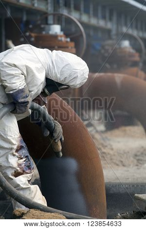 Worker in protective equipment cleans the metal construction before painting them