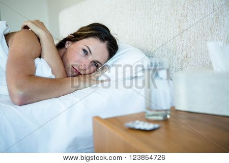 Woman lying in bed next to water and pills on her bedside table