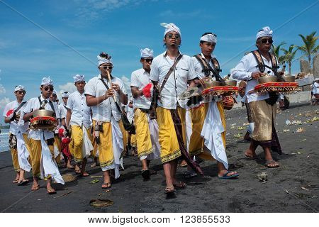 BALI INDONESIA - March 6 2016: Young Balinese Hindu members of a Gamelan percussion orchestra play music on the beach during a Melasti ceremony on March 6 2016 at Purnama Beach in Bali Indonesia.