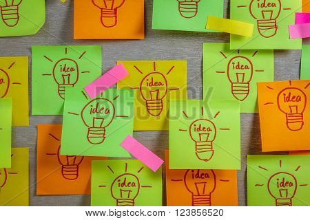 Inspiration concept light bulb idea on colorful sticky note pads .