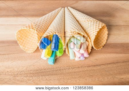 Pastel chalks in wafer cones on wooden background