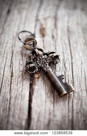 Old rustic key on wooden background