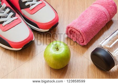 red and grey sneakers with grey shoelaces and red towel green apple bottle with water on wooden background indoors