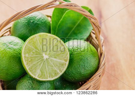 selective focus to slice fresh lime green leaf lime on also many lime in the wood basket.Wood basket on the wood