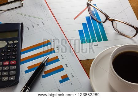 Business summary of the year selective focus pensummary chart calculatorblack coffeepaper clip on wood background.