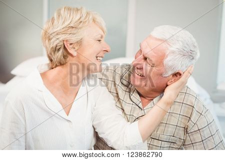 Happy senior woman romancing with husband in nightwear at home