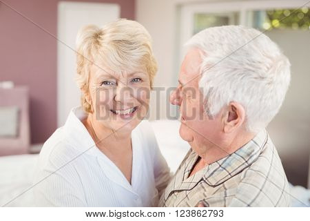 Cheerful senior woman with husband in nightwear at home