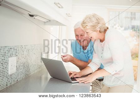 Senior couple laughing while using laptop at counter in kitchen