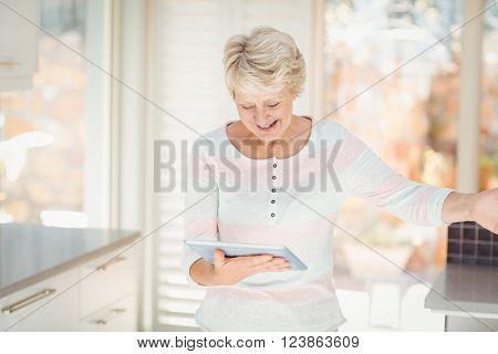 Happy senior woman using digital tablet in kitchen at home
