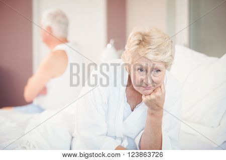 Tensed senior couple on bed at home