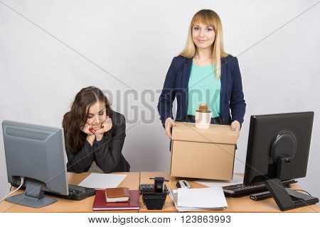 An Employee In The Office Happily Keeps Things Close Sad Colleague
