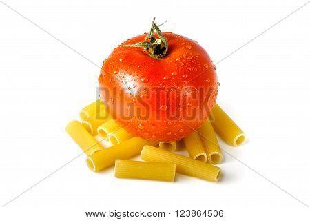 Fresh tomato standing on raw uncooked macaroni isolated on white background