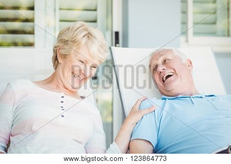 Happy senior couple relaxing on lounge chair at porch