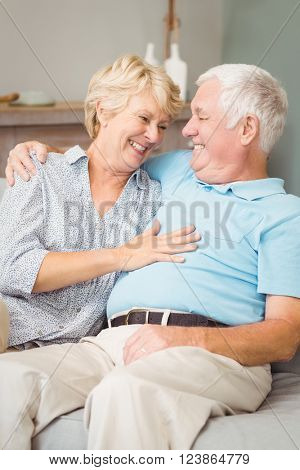 Smiling senior couple looking at eachother while hugging at home