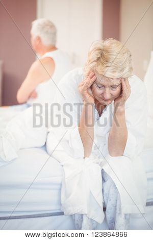 Tensed senior couple in bedroom at home
