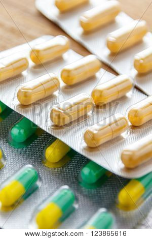 antibiotic capsule drugs in the packaging on wood background. ** Note: Shallow depth of field