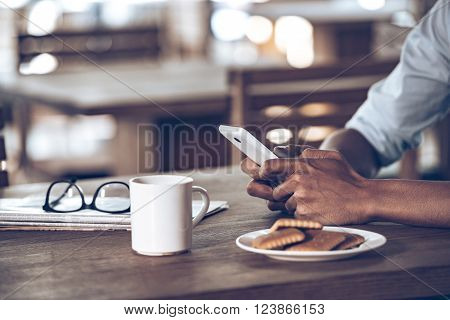His essentials. Close up part of young African man using his smartphone while sitting at wooden table in caf