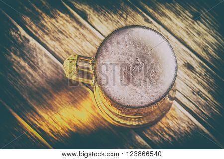 Mug of beer on a wooden background