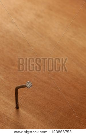 Selective focus unsuccessful to hit the nail.Bent nail on the wood.