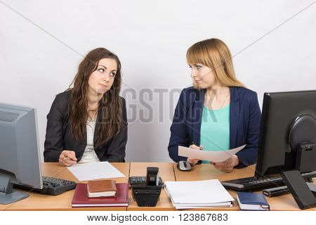 Two Office Employee Sitting At A Desk And A Hostile Look At Each Other
