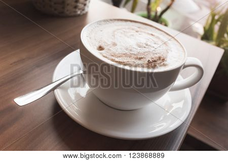 Coffee With Milk Foam Stands On Wooden Table