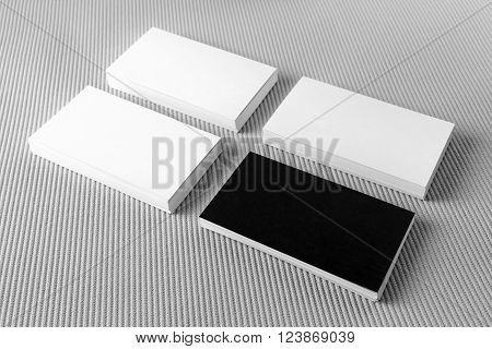 Photo of blank black and white business cards with soft shadows on gray background. Template for branding identity. For design presentations and portfolios.