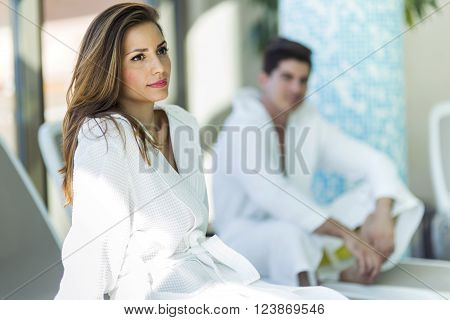 Portrait of a beautiful young woman in a bathrobe next to a swimming pool