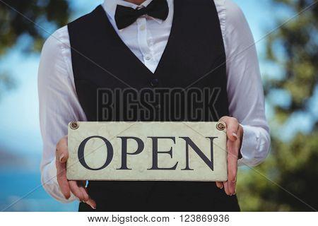 Waitress holding open sign in the garden