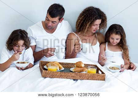 Family having breakfast in bed at home