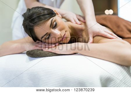 Beautiful woman lying on a massage table and relaxing while being massaged