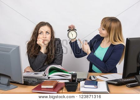 Office Employee Working At The End Of The Day, One With A Smile, Indicating The Clock, The Other Tho