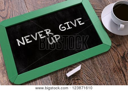 Never Give Up Handwritten on Green Chalkboard. Business Concept. Composition with Chalkboard and Cup of Coffee. Top View Image. 3D Render.