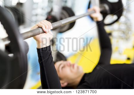 Closeup of young handsome male doing exercises on a bench press