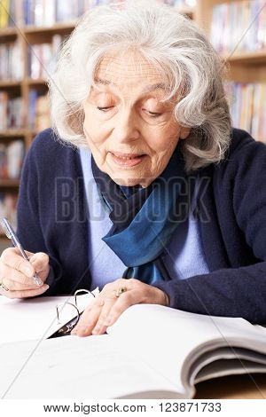 Senior Woman At Desk Studying In Library